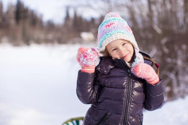 雪の晴れた冬の日のかわいい女の子の肖像画