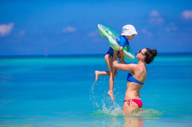 母と娘の熱帯のビーチで時間を楽しんで