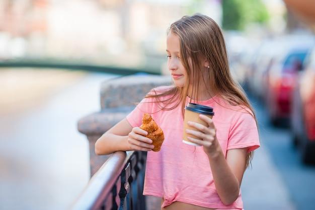 クロワッサンと遊歩道で屋外のコーヒーを持つ少女
