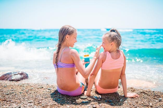 Счастливые дети, применяя солнцезащитный крем друг к другу на пляже. концепция защиты от ультрафиолетового излучения