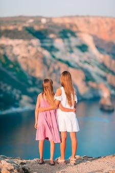 崖の端に屋外の小さな女の子が山の頂上の岩の景色を楽しむ