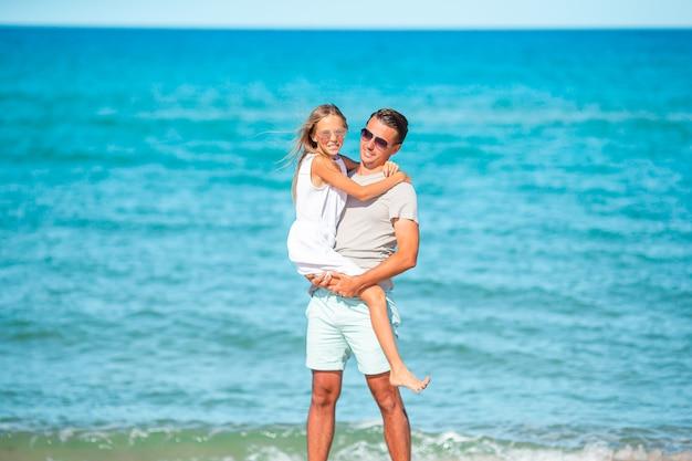 幸せな父と楽しい白い砂浜で彼の愛らしい小さな娘