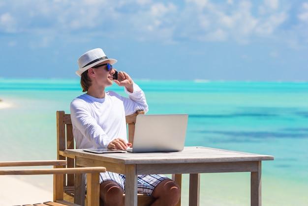 タブレットコンピューターと熱帯のビーチでの携帯電話を持つ若者