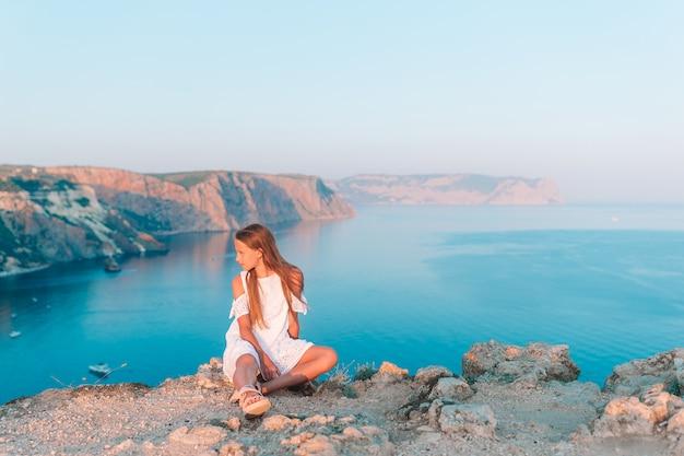 崖の端に屋外の小さな女の子は山の頂上の岩の景色を楽しむ