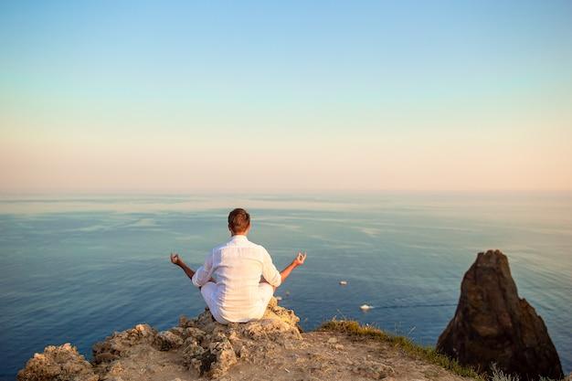 Человек в белом на открытом воздухе на краю обрыва наслаждаться видом на вершину горы рок