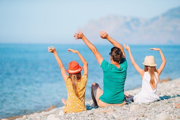 Отец с детьми на пляже, наслаждаясь летом. семейный отдых