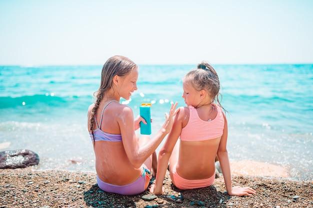 Девушки наносят солнцезащитные кремы друг на друга на пляже. концепция защиты от ультрафиолетового излучения