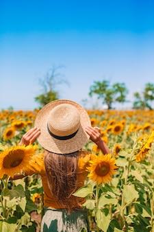 ひまわり畑に麦わら帽子立っている女の子の背面図。夏の時間。