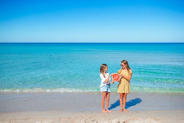 ビーチで楽しんで、スイカを食べて幸せな女の子