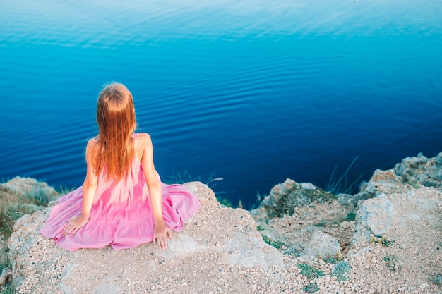 Милая девушка на горе, потрясающие скалы и море на закате. красивая природа
