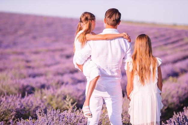 Семья в поле цветов лаванды на закате в белом платье и шляпе