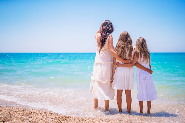 Прелестные маленькие девочки и молодая мать на тропическом белом пляже