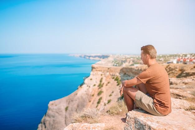 崖の端に屋外の幸せな男は山の頂上の岩の景色を楽しむ