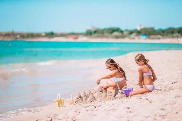 若い美しい母親と彼女の愛らしい小さな娘が熱帯のビーチで楽しい時を過す