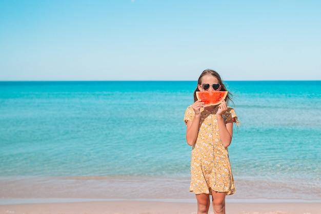 愛らしい少女が休暇中に熱帯のビーチで楽しい時を過す