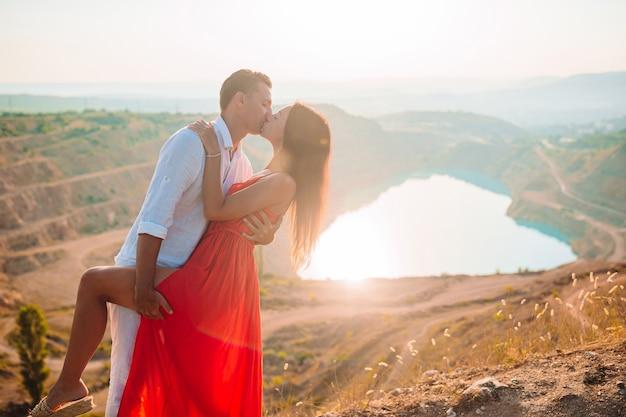 新婚旅行の心のように湖の近くの愛のカップル。ヨーロッパの休暇の概念。美しい風景