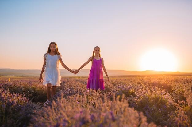 夕暮れ時のドレスでラベンダーの花のフィールドの子供たち