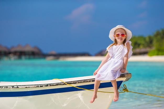 ビーチでの休暇に帽子の愛らしい幸せな笑みを浮かべて少女