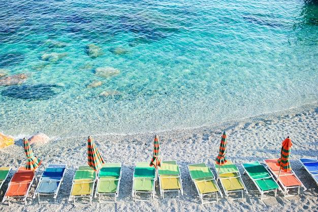 イタリアの海岸に閉じた傘を持つ空のビーチ