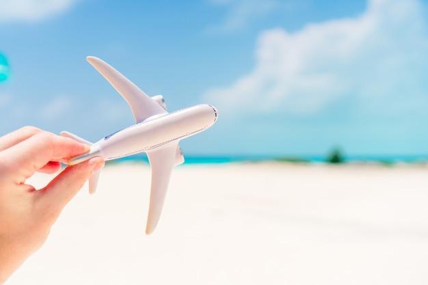 ターコイズブルーの海の背景に小さな白いおもちゃの飛行機