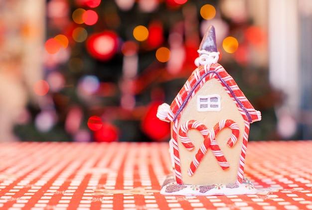 ガーランドと明るいクリスマスツリーとカラフルなキャンディーで飾られたジンジャーブレッドの妖精の家