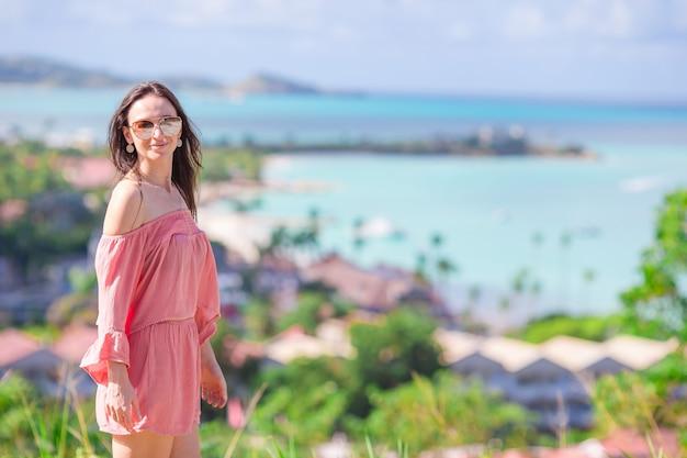 Молодая туристическая женщина с видом на залив на тропическом острове в карибском море
