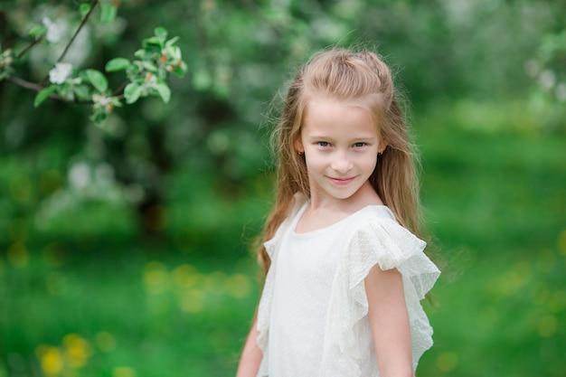 美しい春の日に咲くアップルガーデンのかわいい女の子