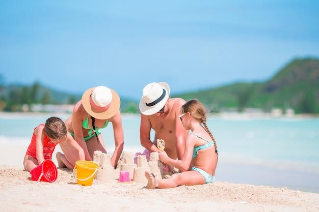 熱帯の白いビーチで家族を作る砂の城