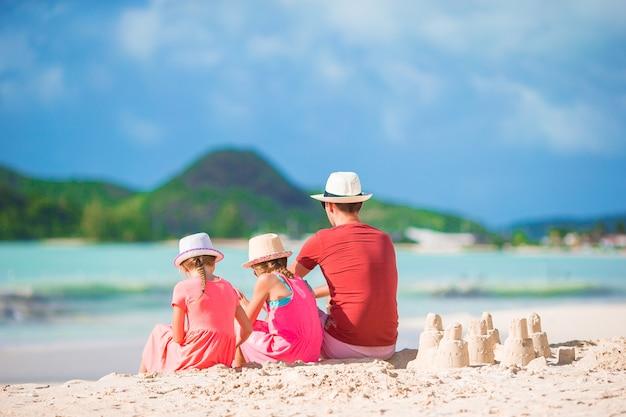 父と小さな子供が熱帯のビーチで砂の城を作る
