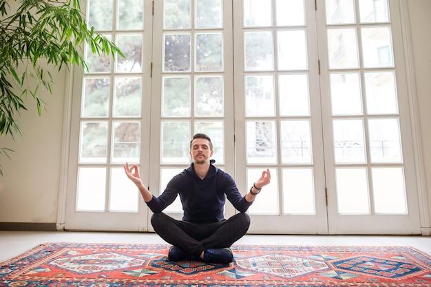 Молодой человек сидит в позе лотоса в помещении