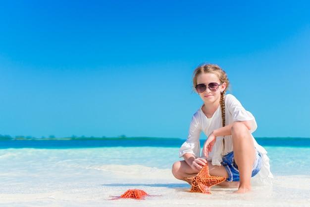 白い空のビーチでヒトデと愛らしい少女