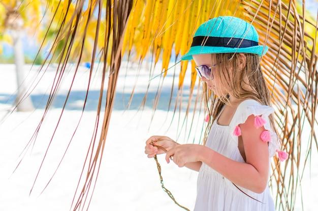 ビーチで大きなココナッツと小さな幸せな女の子
