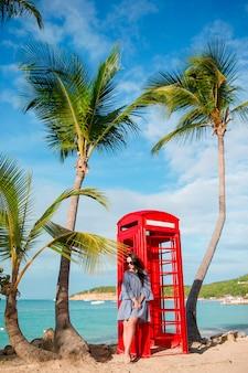 Красивая женщина возле красной телефонной будки в бухте диккенсона антигуа.
