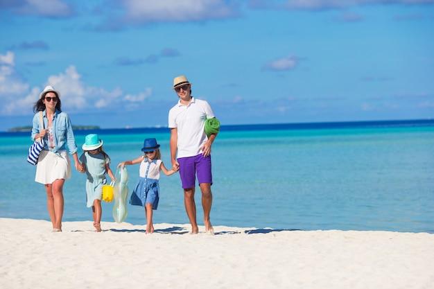 Счастливая красивая семья на белом пляже во время летних каникул