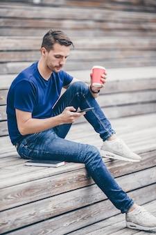 男は公園を歩いている間携帯電話でテキストメッセージを読んでいます。