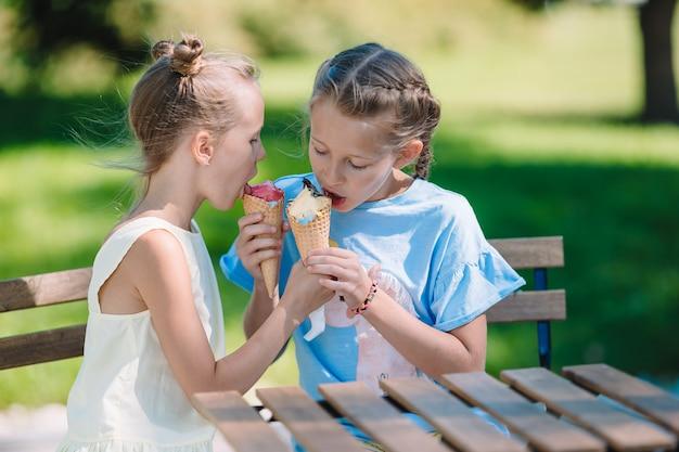Маленькие девочки едят мороженое на улице летом в кафе на открытом воздухе