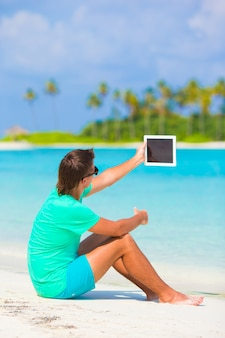 熱帯のビーチでのラップトップを持つ若者