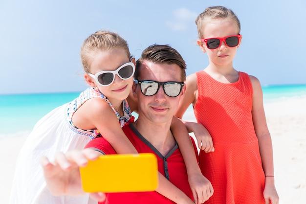 Молодая красивая семья, принимая селфи портрет на пляже