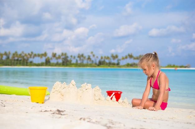 Маленькая девочка играет с игрушками пляж на летние каникулы