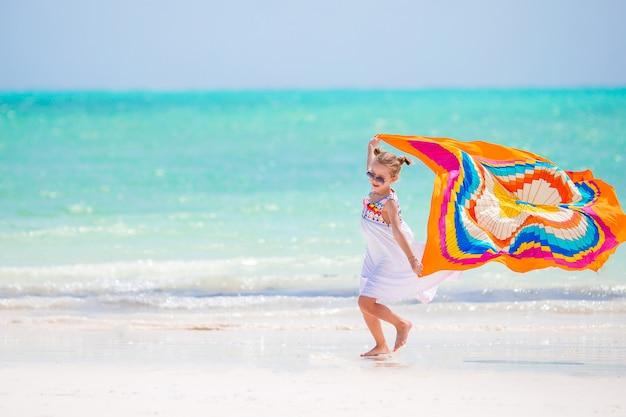 Счастливая маленькая девочка с удовольствием работает с парео на тропическом белом пляже