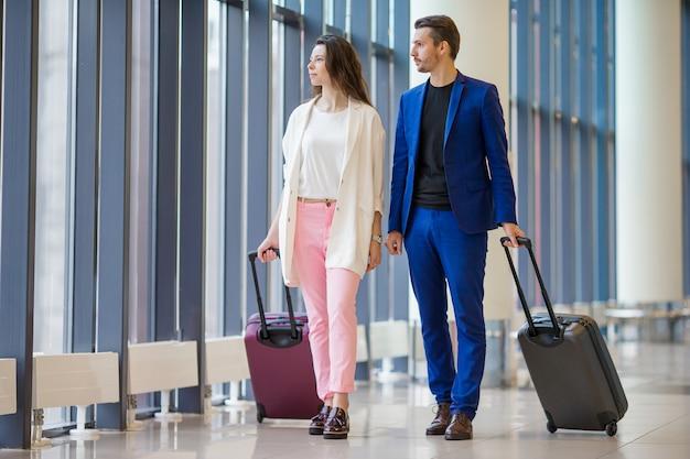 Туристы пара с багажом в международном аэропорту.