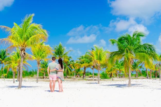 屋外白いビーチで若いカップル。幸せな家族はヤシの木立で彼らの新婚旅行を楽しむ