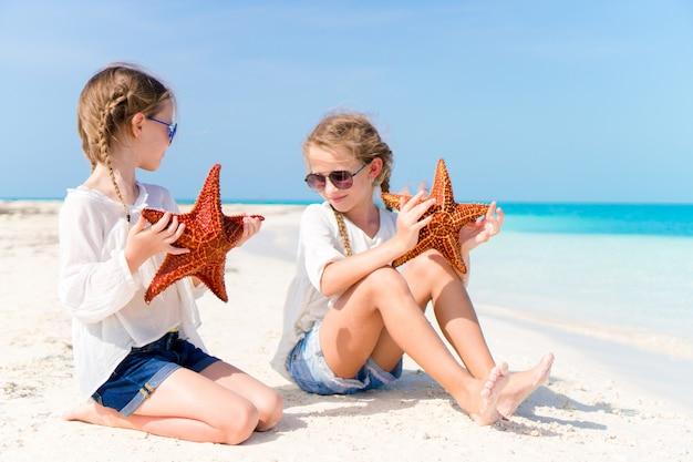 白い空のビーチでヒトデの愛らしい女の子