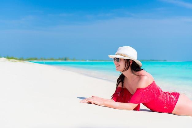 Молодая красивая девушка, лежа на пляже в мелкой тропической воде
