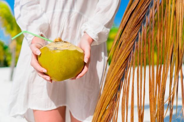 ビーチで暑い日にココナッツミルクを飲む若い女性。パームツリーの近くの女性の手でクローズアップココナッツ