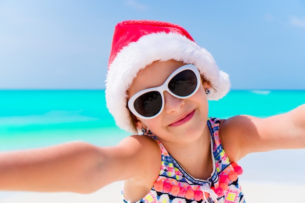 クリスマスのビーチでの休暇中にサンタの帽子のかわいい女の子
