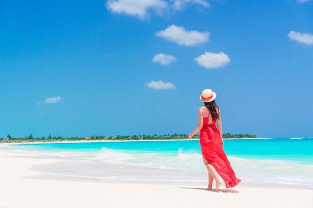 熱帯の海岸で若くてきれいな女性。赤いドレスの少女の背面図