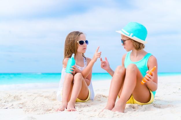Дети наносят солнцезащитный крем друг на друга на пляже. концепция защиты от ультрафиолетового излучения