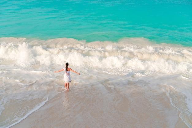 浅い水の中で多くの楽しみを持っているビーチで若い女性。柔らかな光の海岸で美しい少女のトップビュー