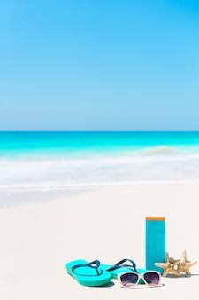 日焼け防止に必要なビーチアクセサリー。サンクリームボトル、ゴーグル、ビーチサンダル、オーシャンビューの白い砂浜のヒトデ